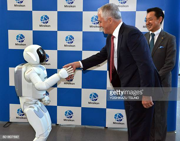 Australian Prime Minister Malcolm Turnbull shakes hands with Japanese auto giant Honda Motor's humanoid robot Asimo while museum head and former...