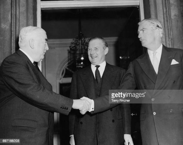 Australian Prime Minister Robert Menzies shakes hands with British Prime Minister Anthony Eden as Foreign Secretary Selwyn Lloyd looks on after a...
