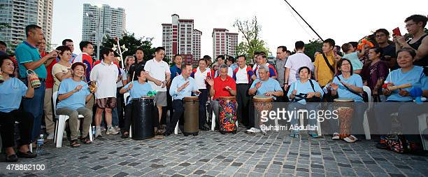 Australian Prime Minister Tony Abbott and Singapore Prime Minister Lee Hsien Loong join in a drum session at Bishan Park on June 28 2015 in Singapore...