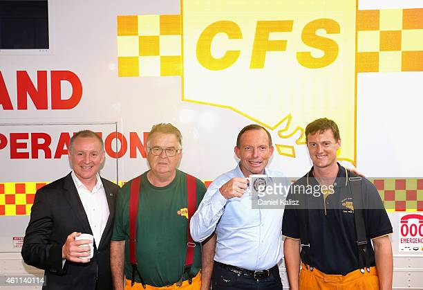 Australian Prime Minister Tony Abbott and South Australia Premier Jay Weatherill pose for a photo with Country Fire Service volunteer's on January 8...