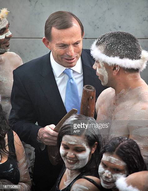 Australian Prime Minister Tony Abbott holds his fighting boomerang while talking to an Aboriginal performer at the opening of the 44th Parliament in...