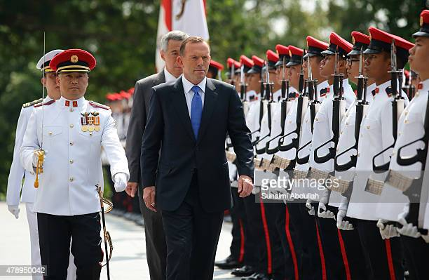 Australian Prime Minister Tony Abbott inspects the guard of honour during the official welcome ceremony accompanied by Singapore Prime Minister Lee...