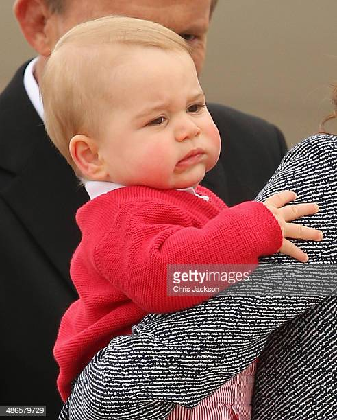 Australian Prime Minister Tony Abbott looks on as Catherine Duchess of Cambridge holds Prince George of Cambridge as they leave Fairbairne Airbase to...