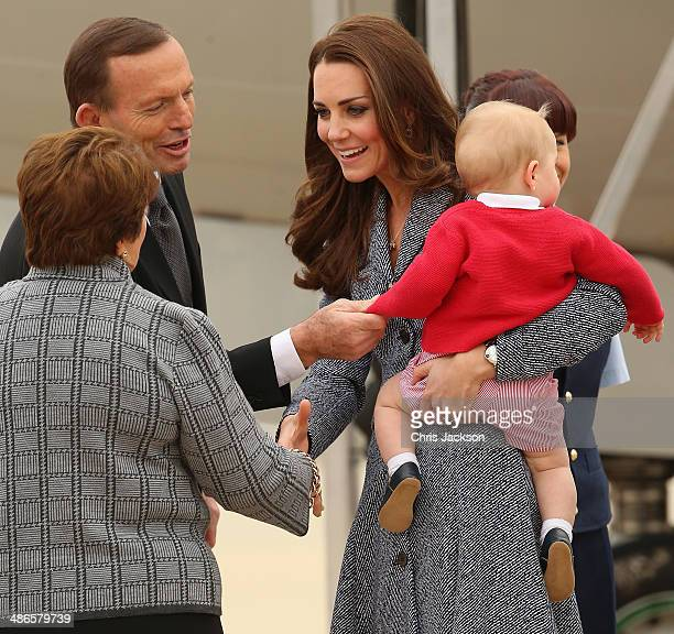Australian Prime Minister Tony Abbott looks on as Catherine, Duchess of Cambridge holds Prince George of Cambridge as they leave Fairbairne Airbase...