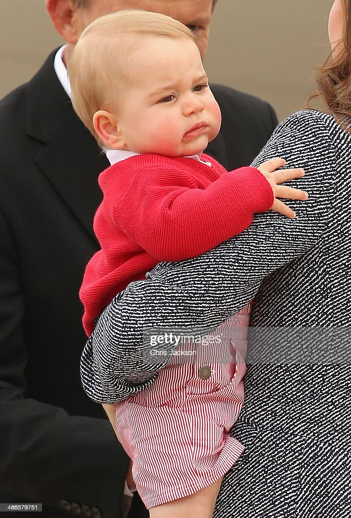 Australian Prime Minister Tony Abbott looks on as Catherine, Duchess of Cambridge holds Prince George of Cambridge as they leave Fairbairne Airbase to head back to the UK after finishing their Royal Visit to Australia on April 25 2014 in Canberra, Australia. The Duke and Duchess of Cambridge are on a three-week tour of Australia and New Zealand, the first official trip overseas with their son, Prince George of Cambridge.