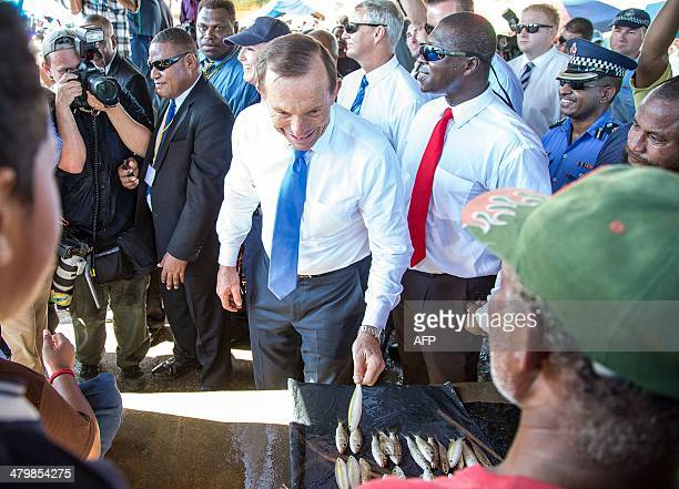 Australian Prime Minister Tony Abbott picks up a fish from a stall during his tour of a market in Port Moresby on March 21 2014 Abbott arrived here...