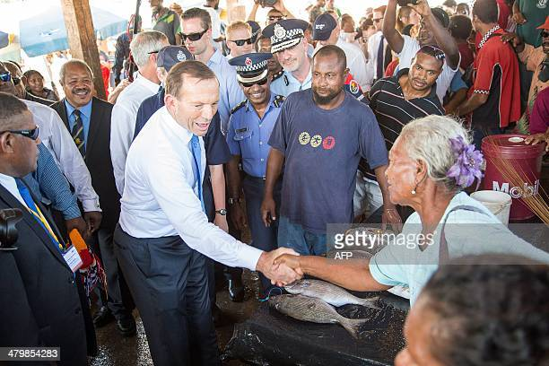 Australian Prime Minister Tony Abbott shakes hands with a local vendor during his tour of a market in Port Moresby on March 21 2014 Abbott arrived...