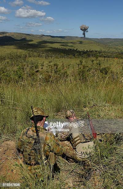 Australian RAAF JTAC members examine their maps as smoke rises from an air strike in the distance that they coordinated on April 6 2016 in Townsville...