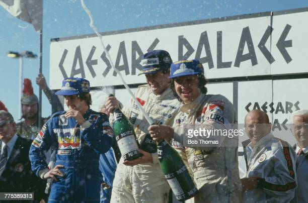 Australian racing driver Alan Jones showers photographers with champagne from the podium after driving the TAG Williams Racing Team Williams FW07C...