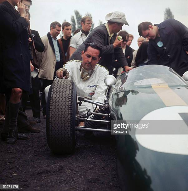 Australian racing driver Jack Brabham checking a tyre on his car at Crystal Palace London 1969