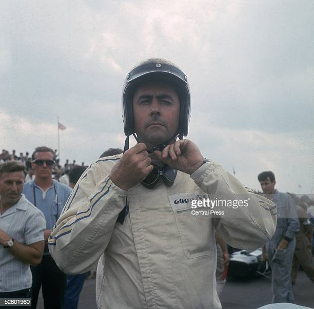 Australian racing driver Jack Brabham fastening his helmet at Silverstone July 1967 the year that Brabham team won their second consecutive...
