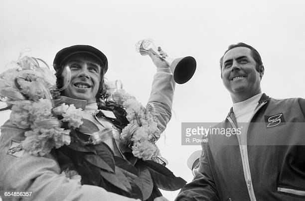 Australian racing driver Jack Brabham founder of the Brabham racing team with Scottish racing driver Jackie Stewart who has just won the British...