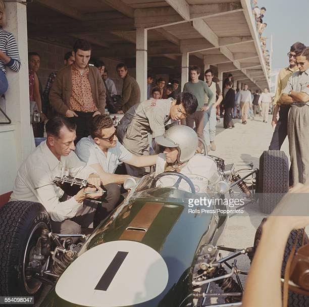 Australian racing driver Jack Brabham sits in his Brabham BT21 Honda RA302E talking to designer Ron Tauranac during the Grand Prix de L'ile de France...