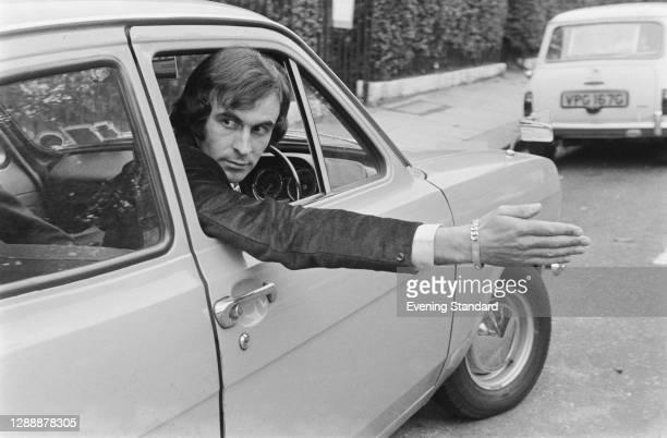 Australian racing driver Tim Schenken signals whilst driving, UK, 1971.