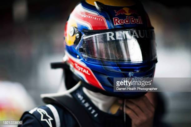 Australian Red Bull Racing Formula One racing driver Mark Webber on the starting grid wearing his crash helmet with a reflective visor while he...