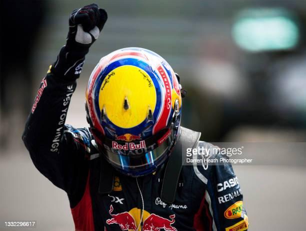 Australian Red Bull Racing Team Formula One team racing driver Mark Webber celebrating winning the race in Parc Fermé by bowing his crash helmet...