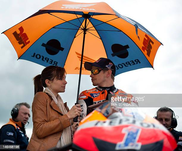 Australian rider Casey Stoner and his wife Adriana Tuchyna wait on the grid ahead of the MotoGP race at the British Grand Prix at Silverstone...