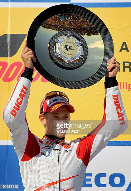 Australian rider Casey Stoner holds the trophy aloft after winning the Australian MotoGP on his Ducati at Phillip Island some 100kms southeast of...