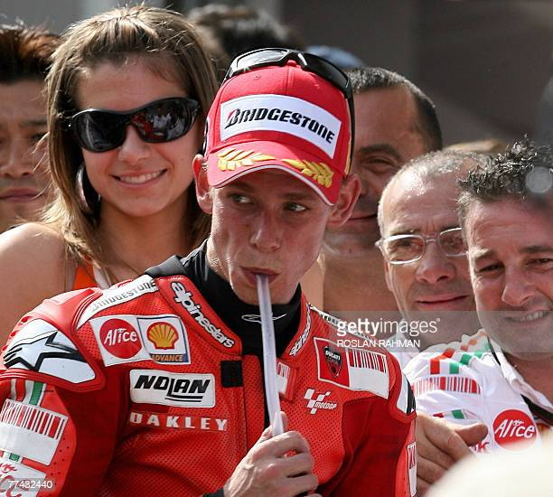Australian rider Casey Stoner of Ducati cooloff as he sips water while his wife Adriana Stoner smiles he won the race at the MotoGP in Sepang...