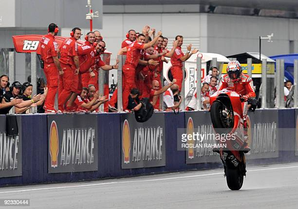 Australian rider Casey Stoner of Ducati wheelies past team members as he celebrates his race victory of the Malaysian Motocycle Grand Prix at the...