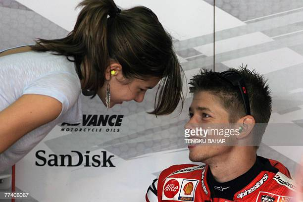 Australian rider Casey Stoner talks to his wife Adrianna Stoner in the team paddock during the first free practice session at the Sepang...