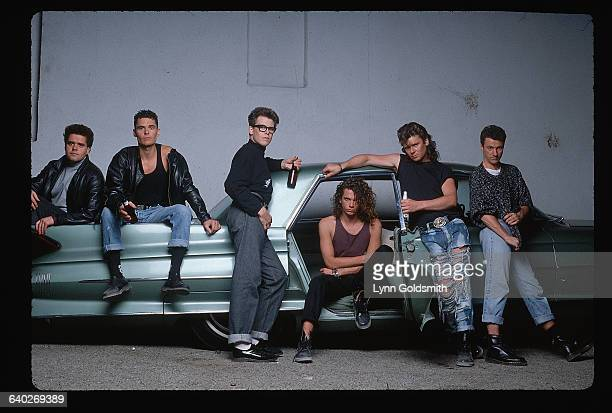 Australian rock group INXS hang out on a vintage automobile From left Andrew Farris Jon Farris Kirk Pengilly Michael Hutchence Tim Farris and Garry...