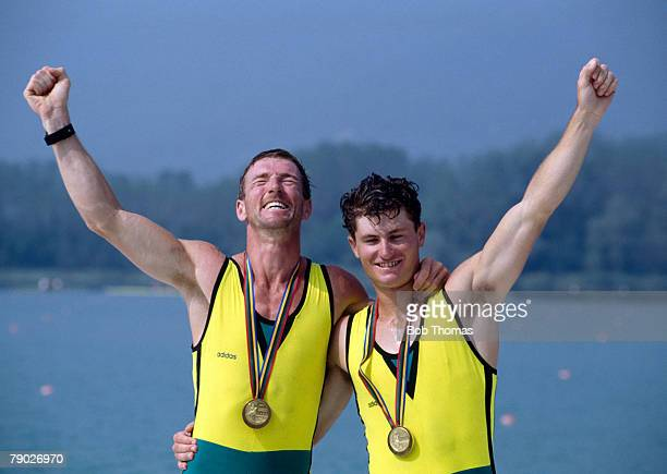 Australian rowers Stephen Hawkins and Peter Antonie stand together on the medal podium after they finished in first place to win the gold medal in...