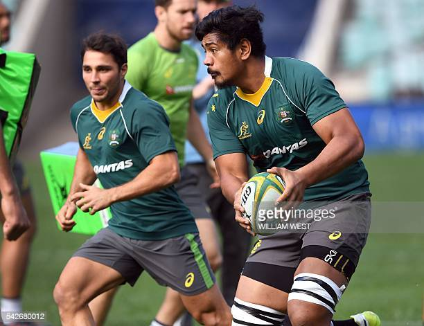 Australian rugby player Will Skelton is assisted by teammate Nick Phipps during the team's captain's run in Sydney on June 24 2016 USE