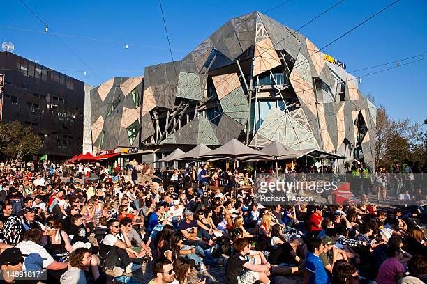 Australian Rules Football supporters watching game on screen in Federation Square.
