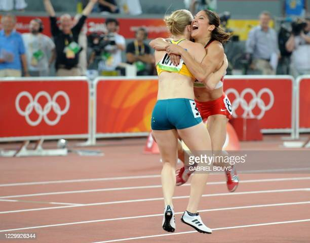 """Australian Sally McLellan and Canada's Priscilla Lopes-Schliep celebrate after the women's 100m hurdles final at the """"Bird's Nest"""" National Stadium..."""
