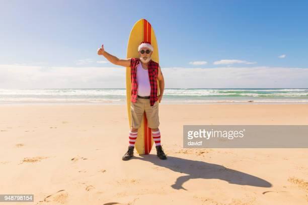 santa australien avec une planche de surf à la plage en été - pere noel humour photos et images de collection