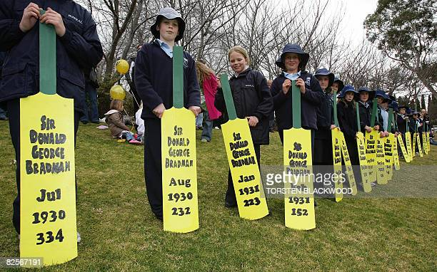 Australian school children displaying the batting scores of cricketer Sir Donald Bradman line the perimeter of Bradman Oval to mark the centenary of...