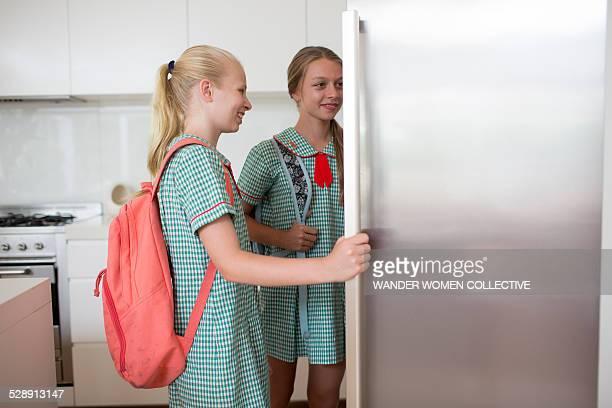 Australian school girls in uniform look in fridge