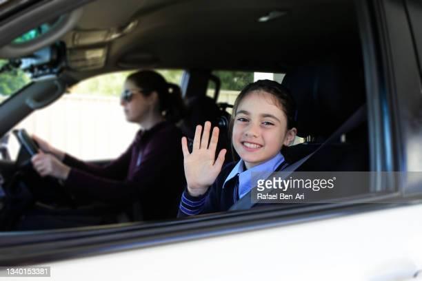australian schoolgirl getting a ride to school by car by her mother - rafael ben ari imagens e fotografias de stock