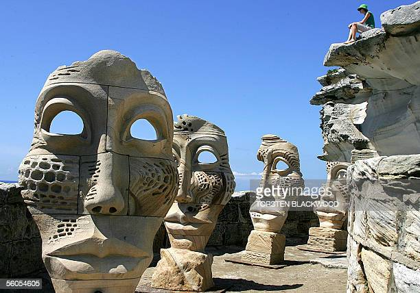 Australian sculptor Michael Purdy's sandstone faces entitled, 'Time and Space 2005', gaze out over a headland on the eve of the opening of the ninth...