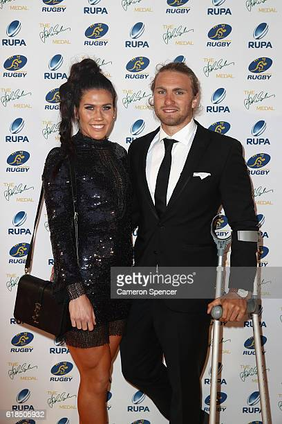Australian Sevens player Charlotte Caslick poses with partner and Australian Sevens player Lewis Holland arrive at the 2016 John Eales Medal at Royal...