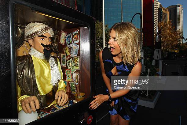 Australian singer and Nissan LEAF ambassador Natalie Bassingthwaighte inserts money into a petrol bowser fashioned into a Zoltar machine at Customs...