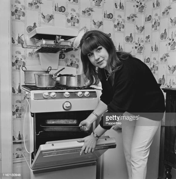Australian singer Judith Durham of folk music group The Seekers, pictured cooking a meal in her kitchen at home in October 1965.