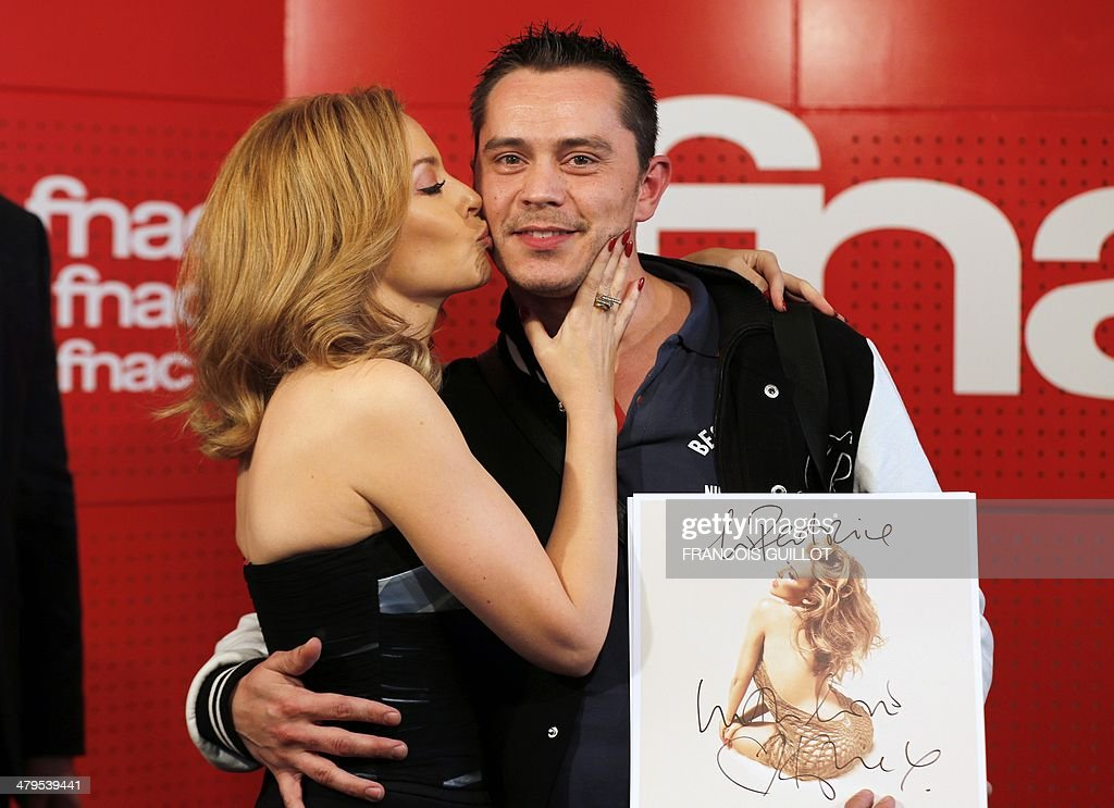 Australian singer Kylie Minogue kisses a fan during a dedication session on March 19, 2014 in Paris.
