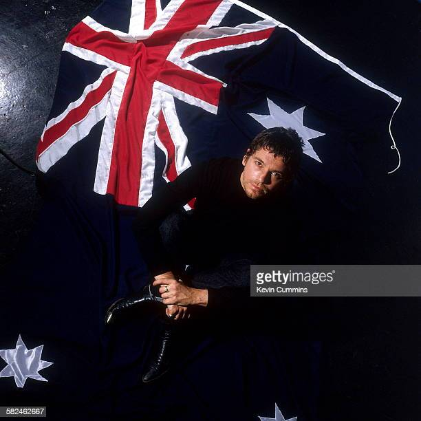 Australian singer Michael Hutchence of Australian rock group INXS sitting on an Australian flag 1997