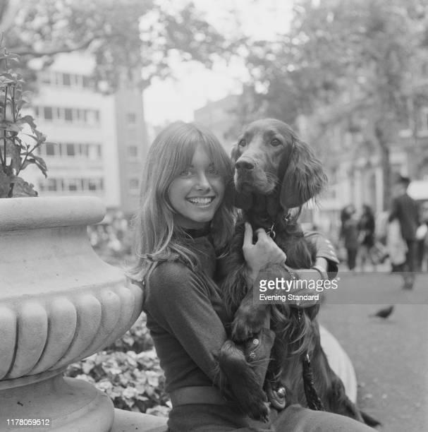 Australian singer Olivia Newton-John holds a red setter dog in Leicester Square, London on 4th September 1970.