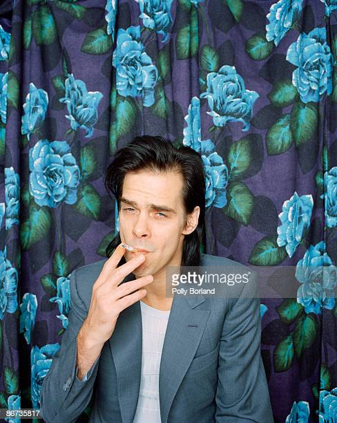 Australian singersongwriter and musician Nick Cave poses against a blue floral curtain circa 2000