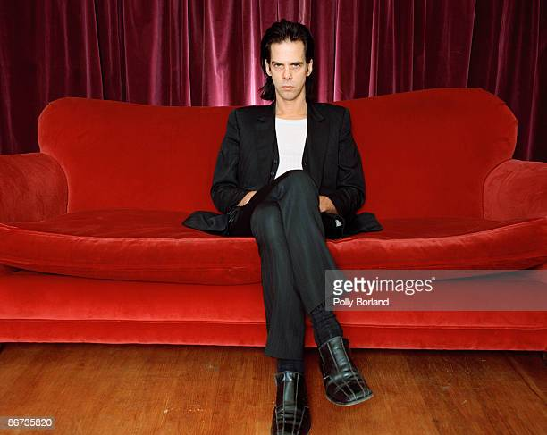 Australian singersongwriter and musician Nick Cave seated on a red velvet sofa circa 2000