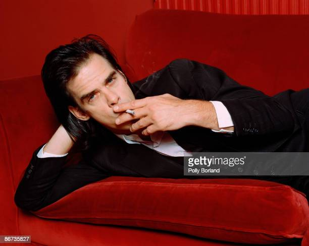 Australian singersongwriter and musician Nick Cave smoking on a red velvet sofa circa 2000
