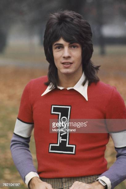 Australian singersongwriter Rick Springfield pictured wearing a red and purple knitted jumper in a park in London in 1973