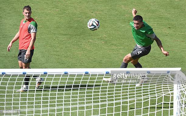 Australian Socceroos football player Tim Cahill heads the ball towards the goal while teammate James Troisi looks on during the team's training...