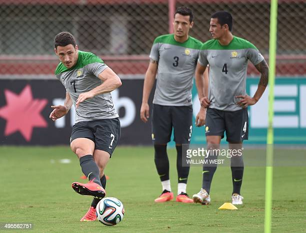 Australian Socceroos player Matthew Leckie passes the ball as teammates Jason Davidson and Tim Cahill look on during a team training run in Vitoria...
