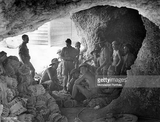 Australian soldiers in a cave during the bombardment of Tobruk in the foreground there are projectiles stacked in containers Tobruk Libya July 1941