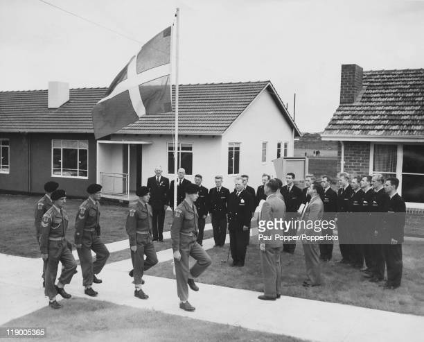 Australian soldiers march past the newly-raised Danish flag, flying outside the Danish team's quarters at the Olympic Village in Heidelberg,...