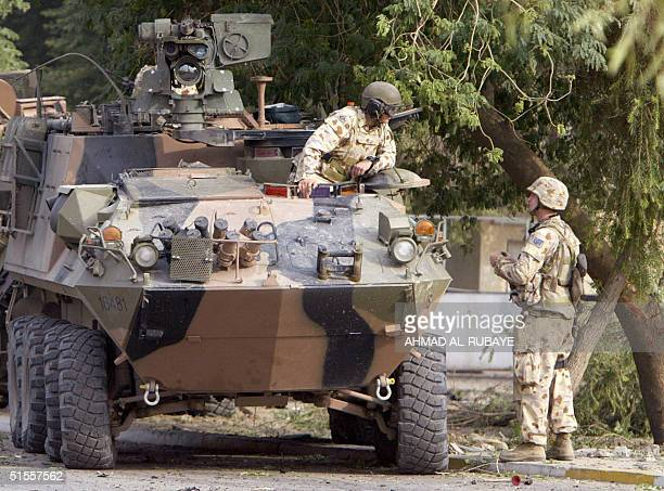 Australian soldiers speak to each other as others carry on securing the area following a blast 25 October 2004 in the Karrada district of Baghdad At...